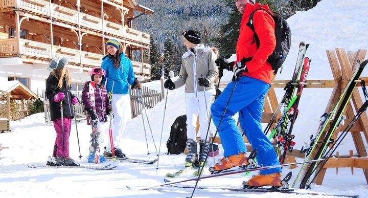 Skifahrer-Familie beim Hotel